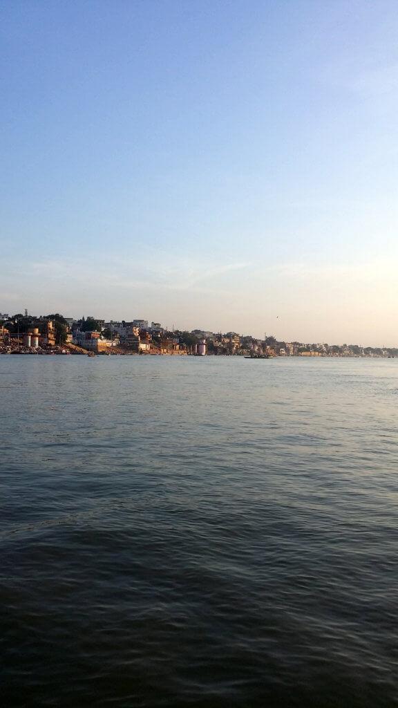 ガンガーの穏やかな水面と朝日を浴びる街並み